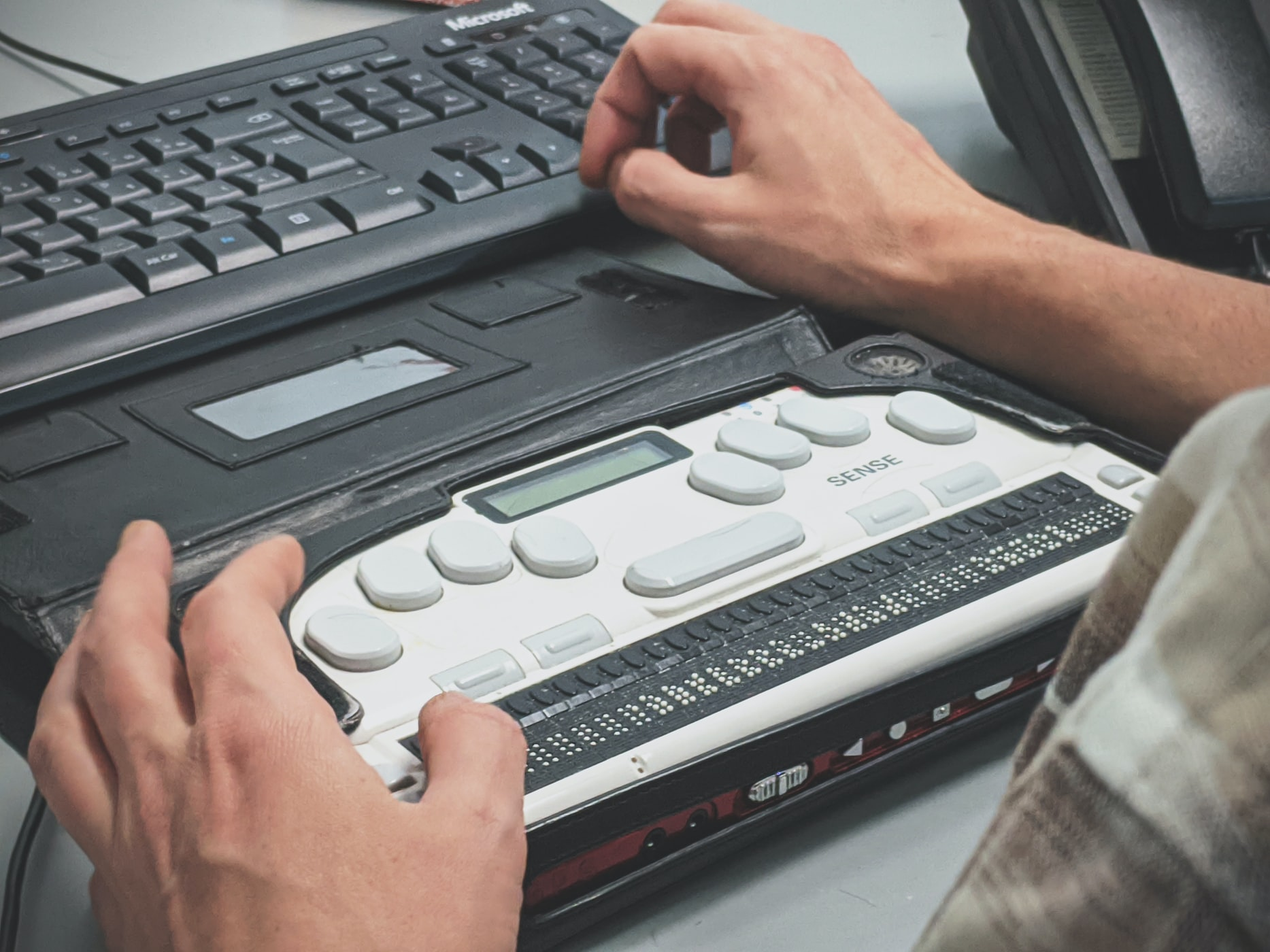 Person using using a braille screen reader.